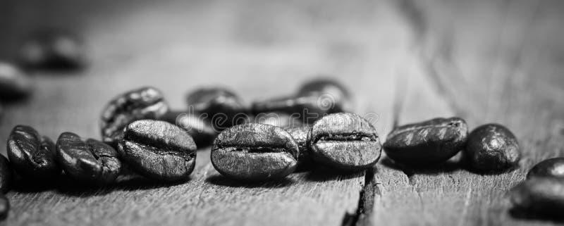 De textuur van koffiebonen op zwart-wit op de houten achtergrond stock afbeeldingen