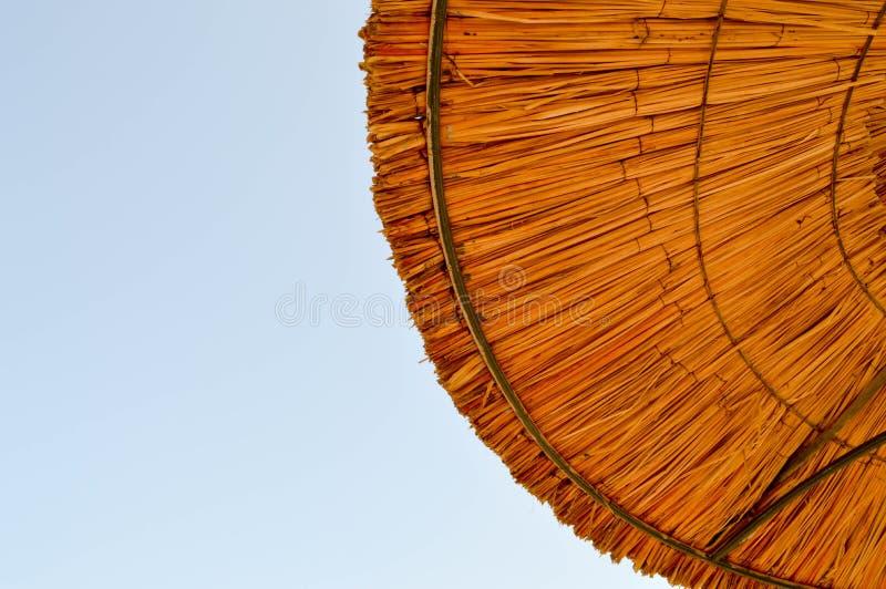 De textuur van de mooie paraplu's van de stro natuurlijke zon maakte van hooi in een tropische woestijntoevlucht, die rusten tege stock foto