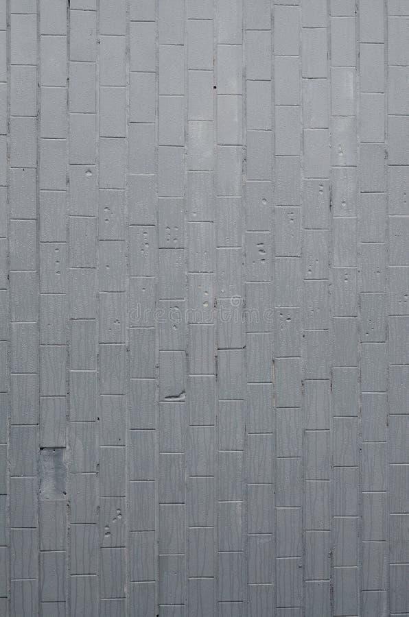 De textuur van de muur van de oude tegel, geschilderde grijs onder de invloed van condensatie Heel wat kleine dalingen en watervl royalty-vrije stock foto