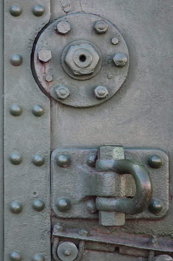 De textuur van de muur van de tank, van metaal wordt en met een massa bouten en klinknagels wordt versterkt gemaakt die die Beeld stock fotografie