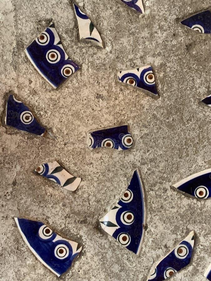 De textuur van de muur, de vloer is grijs met stukken van gebroken blauw porselein met een patroon Grijze concrete vloer met gebr royalty-vrije stock afbeeldingen