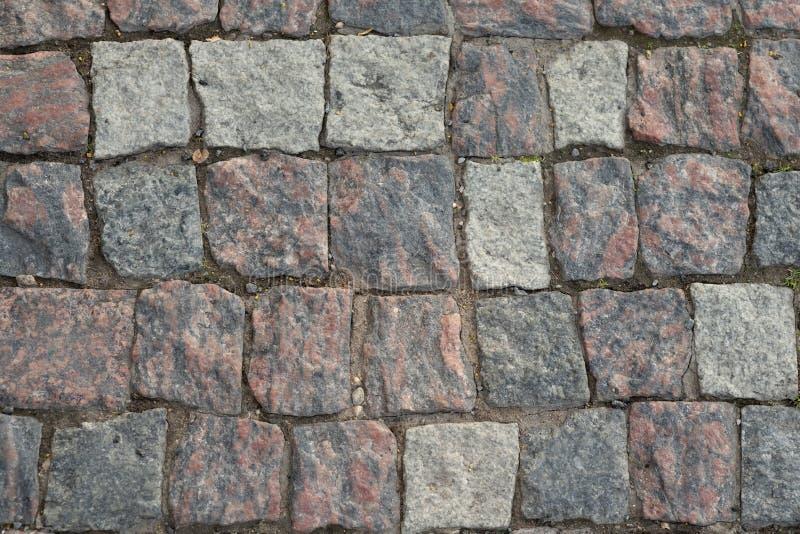 De textuur van de steenbestrating, graniet cobblestoned bestratingsachtergrond, cobbled de regelmatige vormen van de steenweg, ab royalty-vrije stock foto