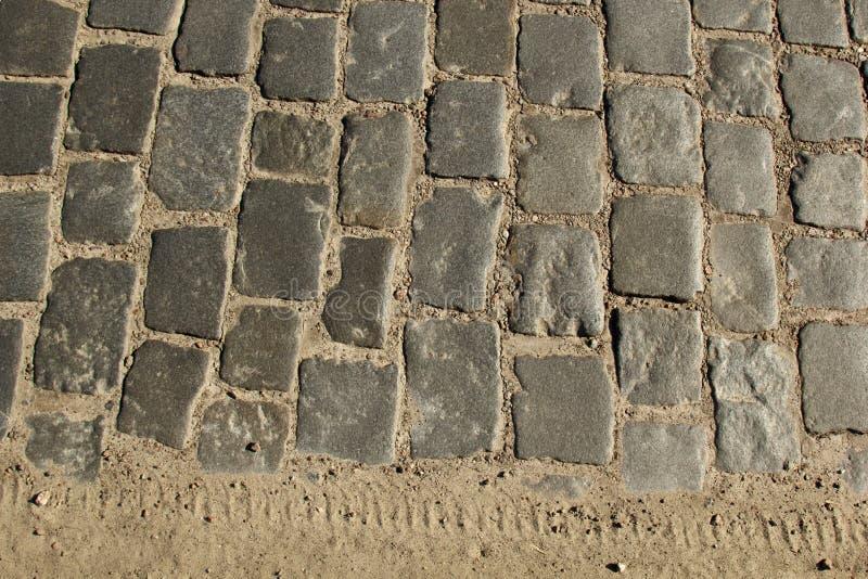 De textuur van de steenbestrating Het graniet cobblestoned bestratingsachtergrond Abstracte achtergrond van het oude close-up van stock foto