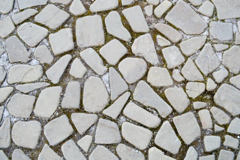 De textuur van de steenweg, bestrating, muren van grote grijze oude middeleeuwse ronde sterke stenen, keien De achtergrond royalty-vrije stock afbeelding