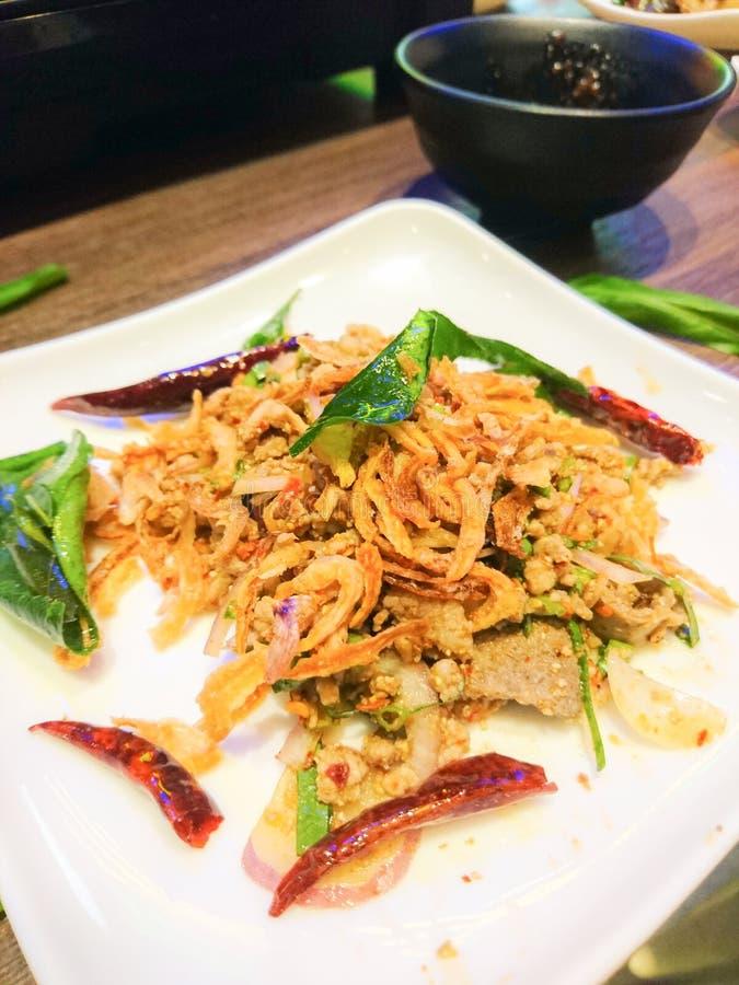 De Thaise Kruidige Fijngehakte Varkensvleessalade met droge geroosterde Spaanse peper en geroosterde kaffir kalk gaat weg stock afbeelding
