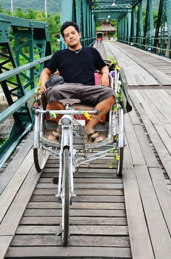 De Thaise Mens zit bij het Berijden van driewieler op Brug over Pai Rive van Mae Hong Son Thailand stock fotografie