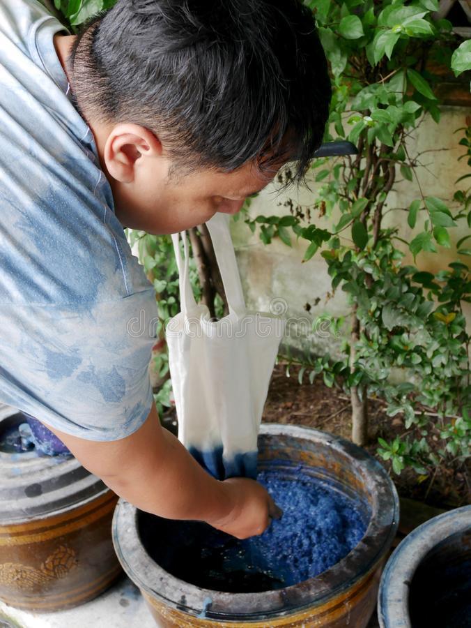 De Thaise mensen binden batik vervend Inheemse Kennis chemische en vloeibare kleurstof Mauhom en indigokleur in pot in Nonthaburi stock foto's