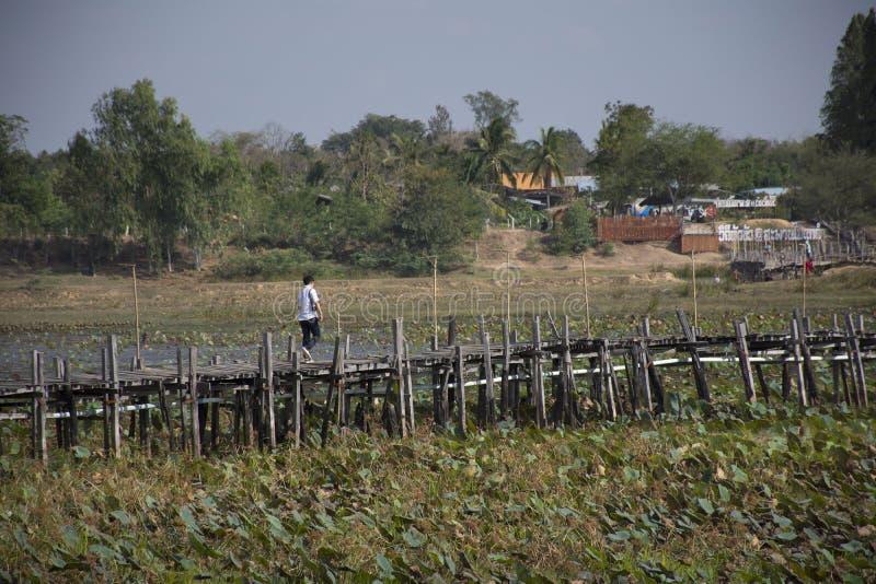 De Thaise mensen en de vreemdelingsreizigers reizen en het lopen het bezoek op de lange houten brug van Kae Dam in Maha Sarakham, royalty-vrije stock foto