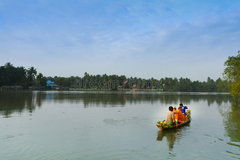 De Thaise monnik paddelt de boot die voedsel op kanaal ontvangen stock afbeelding