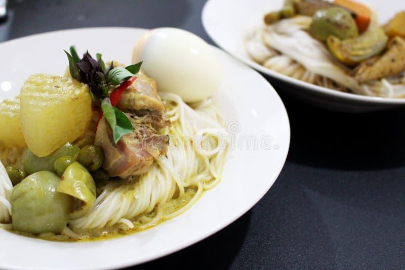 De Thaise noedels van de rijstbloem gezet naast kippen groene kerrie stock fotografie