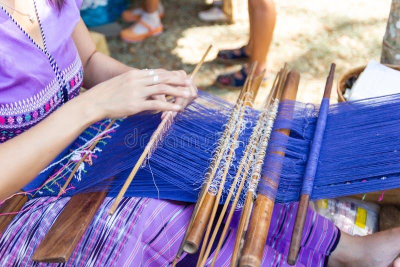 De Thaise Oude vrouwen gebruiken de machine - Huishoudenweefgetouw het weven is Huishoudenberoep stock afbeelding