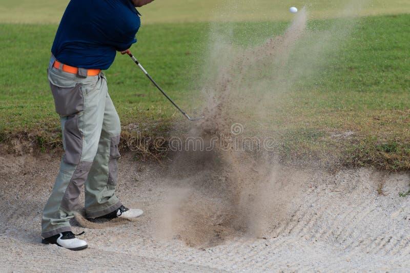 De Thaise speler van het jonge mensengolf in actieschommeling in zandkuil tijdens praktijk vóór golftoernooien bij golfcursus royalty-vrije stock afbeelding
