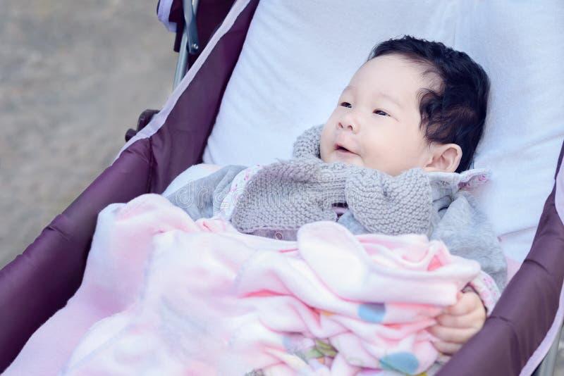 De Thaise zitting van het babymeisje in een purpere wandelwagen stock foto