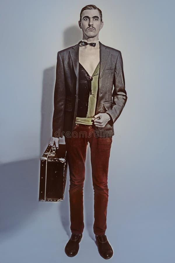 De theateracteur houdt een koffer in zijn hand stock afbeelding