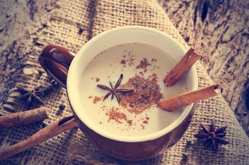 De thee van Masalachai met kruiden en steranijsplant, pijpje kaneel, peperbollen, op zak en houten achtergrond stock foto