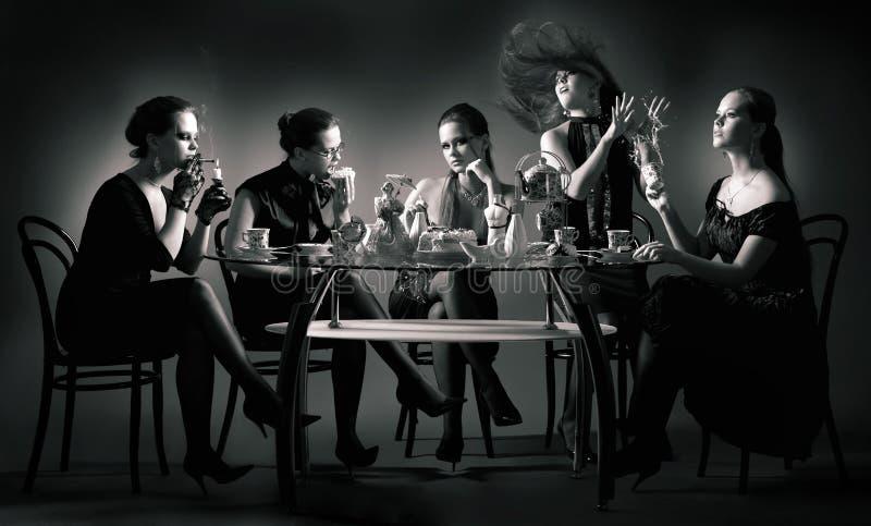 De thee van vijf schoonheidsmeisjes het drinken bij de lijst stock afbeeldingen
