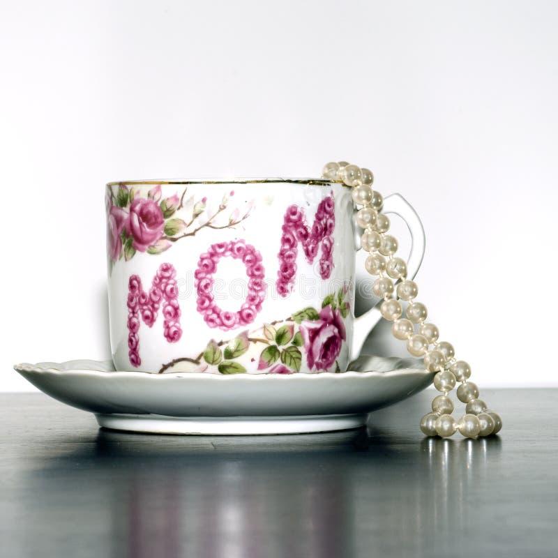 De theekop van de moederdag en parelsvierkant stock afbeeldingen