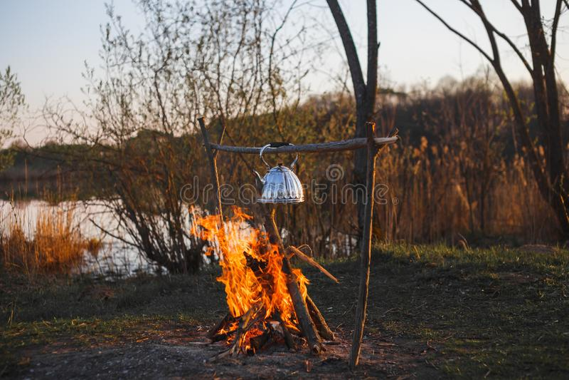 De theepot met thee hangt over de brand op de riverbankzonsondergang royalty-vrije stock foto's