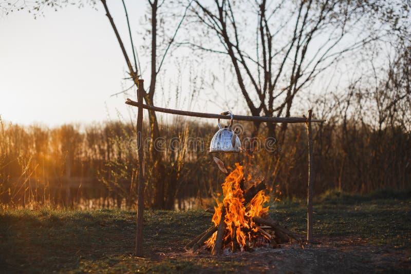De theepot met thee hangt over de brand op de riverbankzonsondergang stock foto