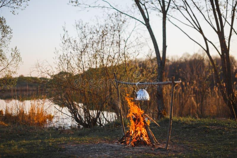 De theepot met thee hangt over de brand op de riverbankzonsondergang royalty-vrije stock afbeeldingen