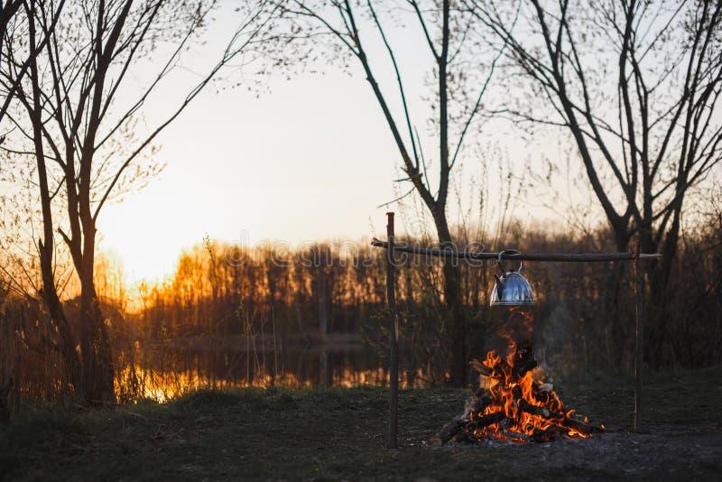 De theepot met thee hangt over de brand op de riverbankzonsondergang stock foto's