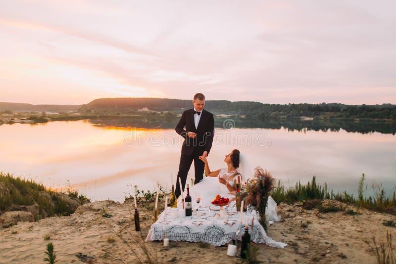 De Thehappyjonggehuwden houden handen tijdens hun picknick dichtbij de rivier tijdens de zonsondergang royalty-vrije stock afbeeldingen