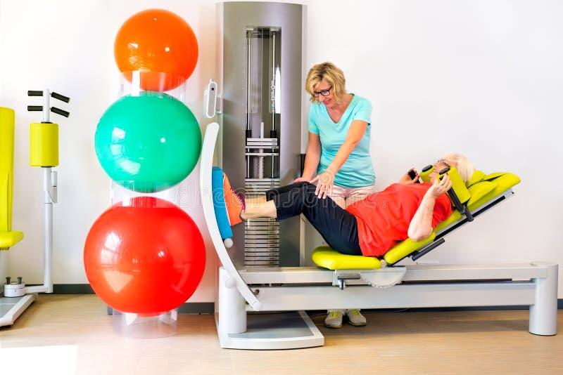 De therapeut helpt vrouw beenspieren versterken stock afbeelding