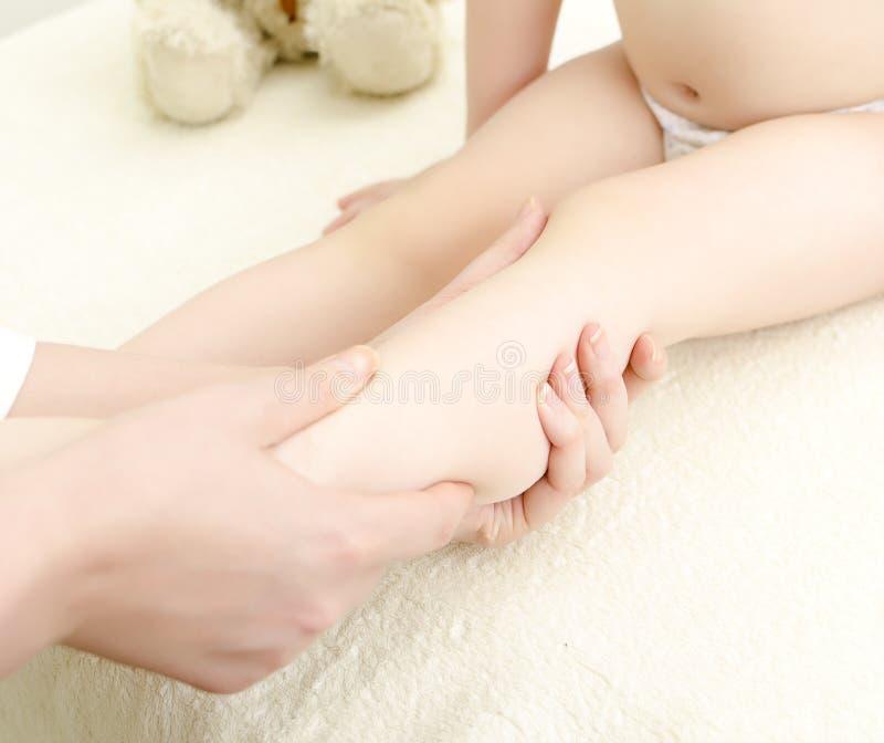 De therapeut maakt een kindmassage. stock afbeelding
