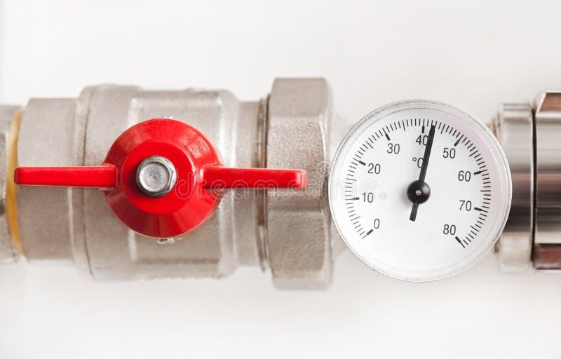 De thermometer van het water met rode klep en metaalpijpen royalty-vrije stock foto