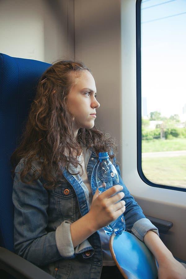 De tiener berijdt een trein met een skateboard in zijn handen royalty-vrije stock afbeelding