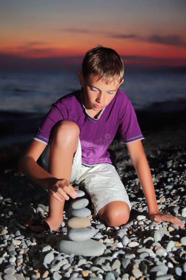 De tiener creërt piramide van kiezelsteen op zeekust royalty-vrije stock afbeelding
