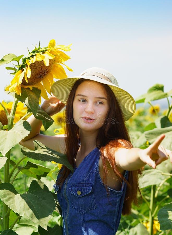 De tiener in denimkleding met glimlach toont op zonnebloem Landbouw gebied Portret stock foto's