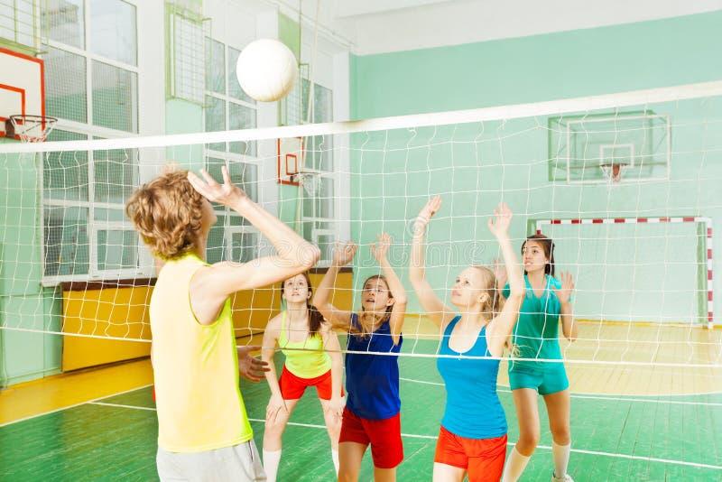 De tiener dienende overhandse bal van de volleyballspeler stock afbeelding