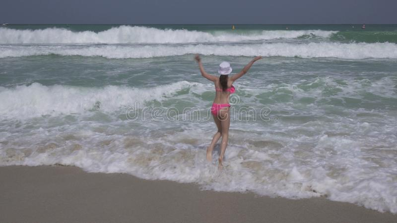 De tiener in een badpak springt gelukkig in golven van Perzisch Golf op strand van Doubai stock foto
