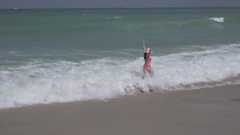 De tiener in een badpak springt gelukkig in golven van Perzisch Golf op strand van Doubai stock fotografie
