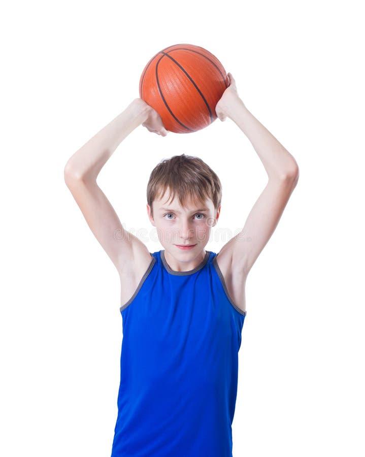De tiener in een blauw overhemd werpt een bal voor basketbal Geïsoleerde stock foto's