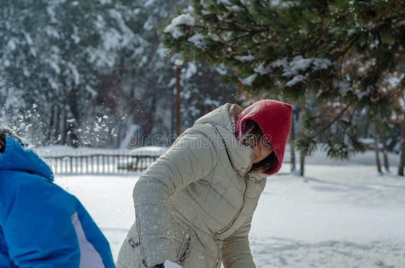 De tiener en haar moeder spelen sneeuwballen stock afbeelding