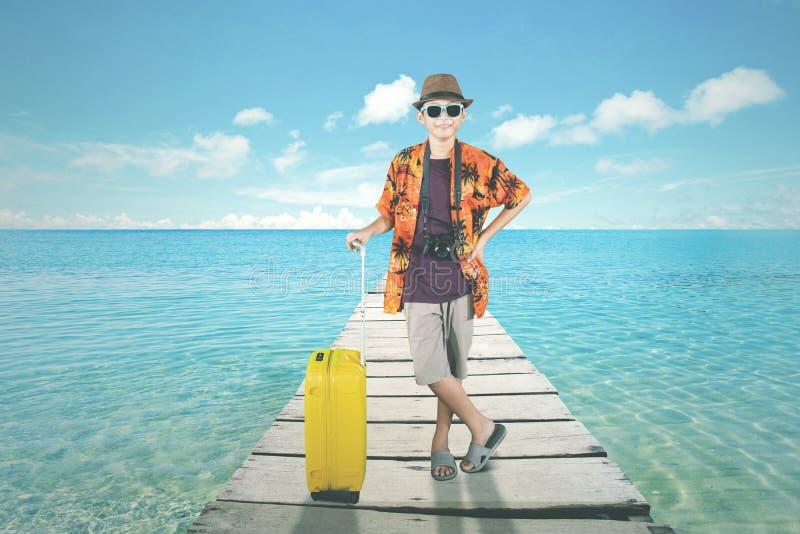 De tiener houdt een bagage op de dokbrug royalty-vrije stock afbeeldingen