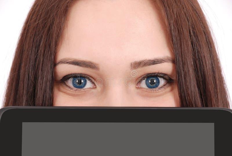 De tiener houdt voor de computer van de gezichtstablet stock afbeelding