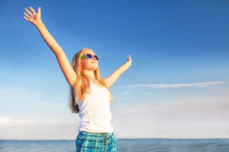 De tiener (meisje) geniet van zonsondergang op de hemelachtergrond stock afbeelding