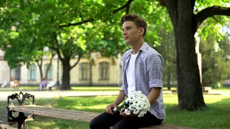 De tiener met boeket van bloemen zit op bank in park, wachtend op meisje stock foto