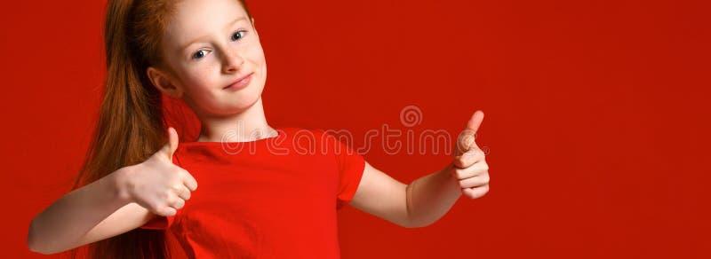 De tiener met gezonde freckled huid, die een rode t-shirt dragen, die de camera bekijken toont grote duimen, gelukkige gelaatsuit royalty-vrije stock afbeelding