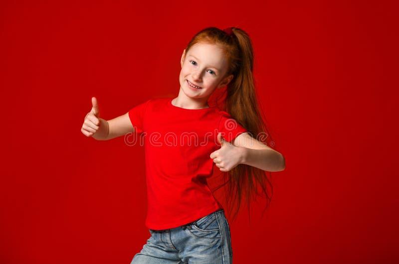 De tiener met gezonde freckled huid, die een rode t-shirt dragen, die de camera bekijken toont grote duimen, gelukkige gelaatsuit royalty-vrije stock fotografie