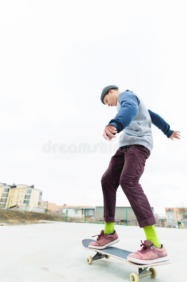 De tiener skateboarder berijdt skatepark in bewolkt weer De jeugd Stedelijke Cultuur stock afbeeldingen