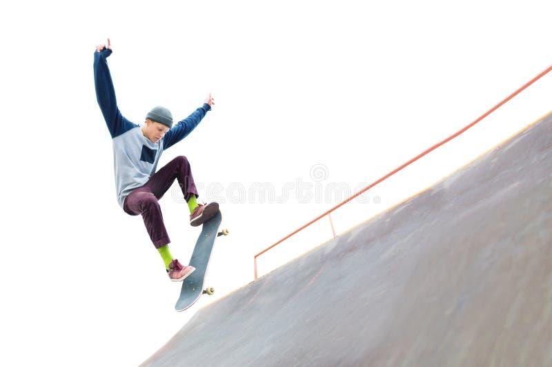 De tiener skateboarder in GLB doet een truc met een sprong op de helling in skatepark Geïsoleerde schaatser en helling  stock foto