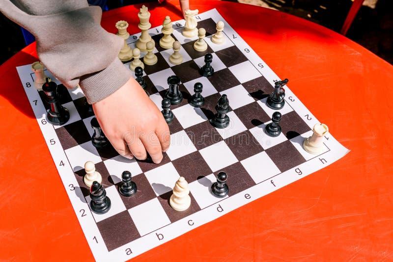 De tiener speelt schaak op de straat De beweging van spelstukken op een schaakbord De ontwikkeling van het denken en logica E stock fotografie