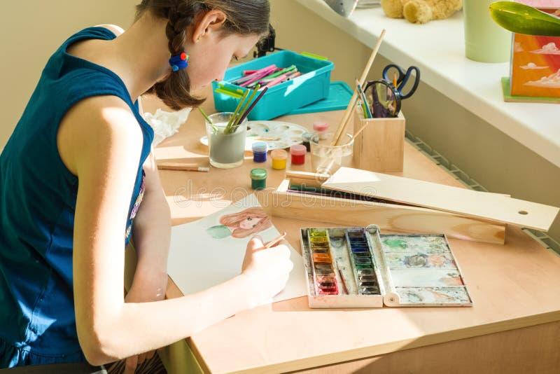 De tiener is thuis bezig geweest met creativiteit, trekkend waterverf bij een lijst in ruimte Kindcreativiteit, recreatie, ontwik royalty-vrije stock afbeeldingen
