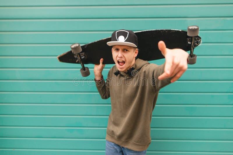 De tiener in de tribunes van straatkleren met een longboard in zijn handen, onderzoekt de camera en haalt emotioneel zijn handen  stock foto