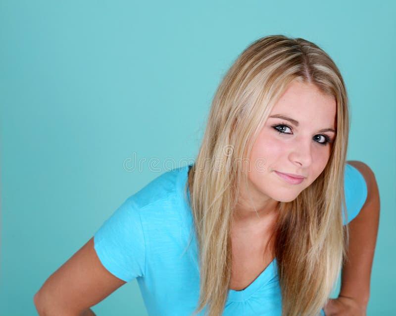 De tiener van de blonde op blauwe achtergrond royalty-vrije stock foto's