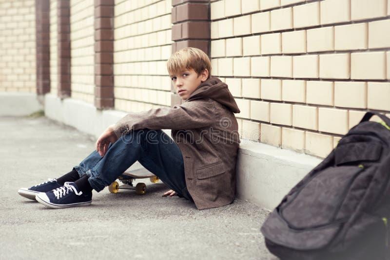 De tiener van de school met schooltas en skateboard royalty-vrije stock afbeelding